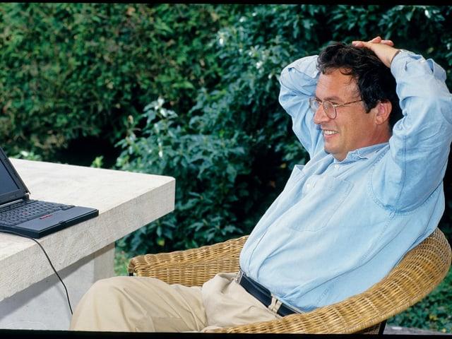 Ein Mann in blauem Hemd sitzt