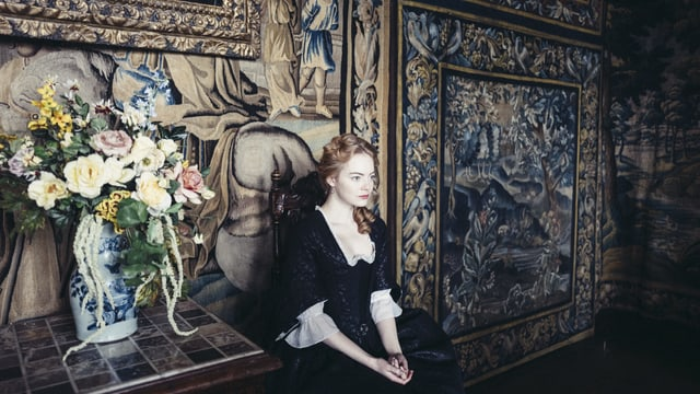 Emma Stone sitzt als Kammerzofe Abigail auf einem Stuhl im Palast.