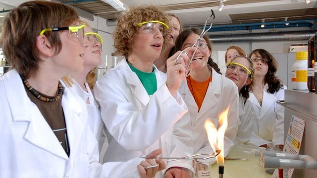 Eine Gruppe von Kindern in weissen Kitteln blicken auf eine Zange über einer Flamme.