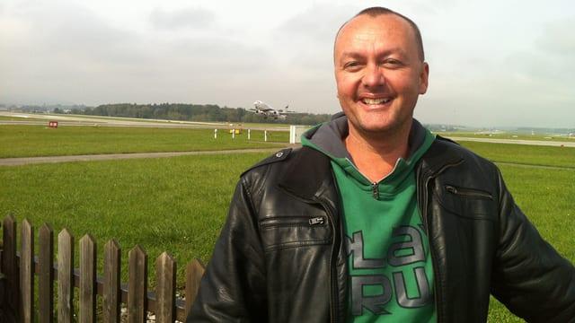 Der Moderator trägt ein grünes Sweatshirt und eine schwarze Lederjacke und steht vor einem Holzzaun.