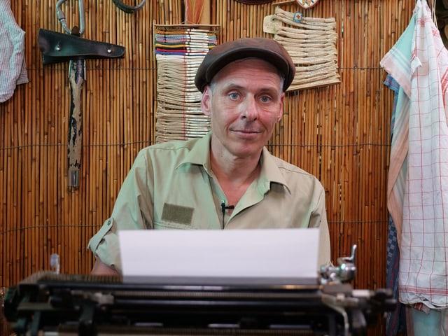 Ein Mann mit Schiebermütze sitzt lächelnd hinter einer alten Schreibmaschine.