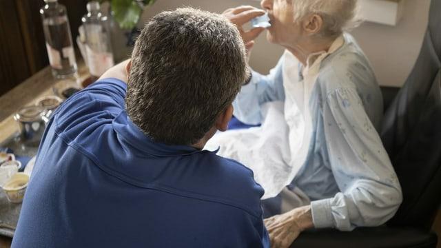 Ein Pfleger verabreicht einer betagten Person ein Medikament.