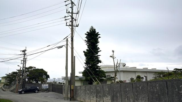 Ein umzäuntes weisses Gebäude, davor ein Leitungsmast.