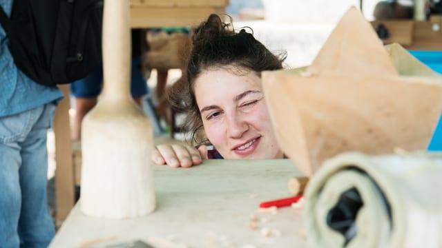Eine junge Frau schielt auf eine Holzskulptur
