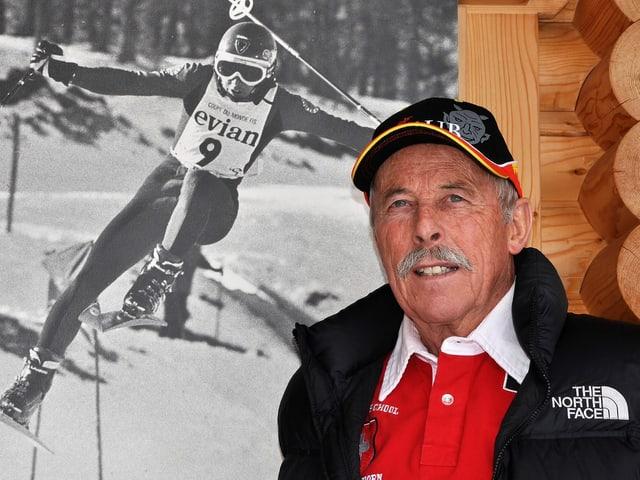 Ein Mann steht neben einer Fotografie, die einen Skirennfahrer zeigt.