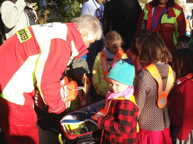 Eine Gruppe Kinder mit einem Rettungssanitäter