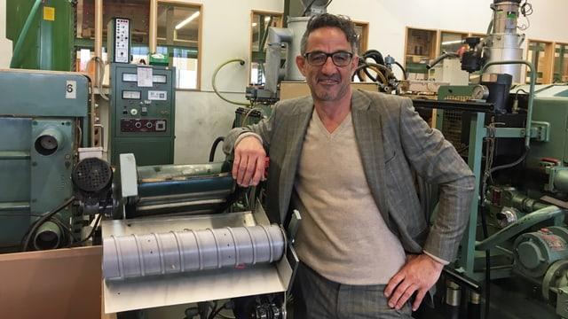 Ein Mann mit Brille lehnt sich auf eine Produktionsmaschine.