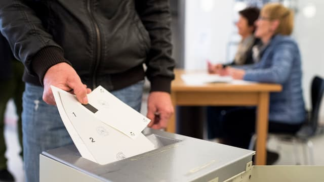 Ein Mann wirft Abstimmungszettel in die Urne
