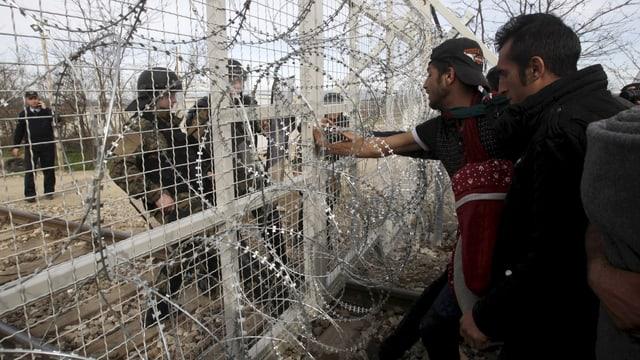 Flüchtlinge blicken durch einen Zaun hindurch zwei Polizisten an.