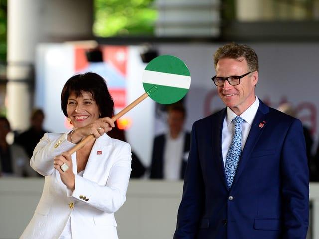 Bundesrätin Leuthard hält ein grünes Strassensignal in der Hand, das die baldige Eröffnung verdeutlichen soll. Neben ihr steht SBB-Chef Meyer.