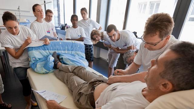 Sieben Auszubildende beobachten an einem Spitalbett den Ausbildner bei der Patientenpflege.