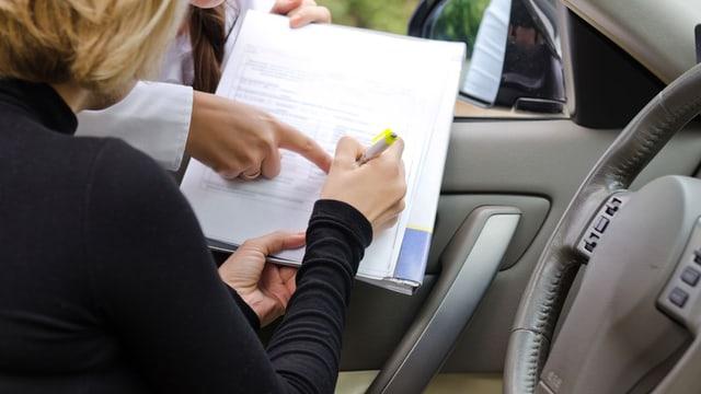 Eine Frau sitzt im Auto und unterschreibt einen Vertrag, den ihr eine Verkäuferin hinhält
