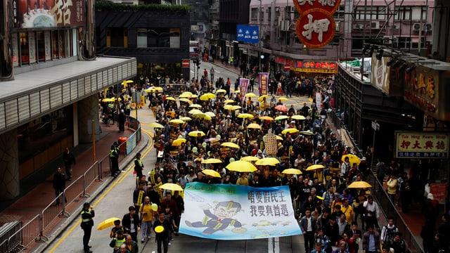 Menschen mit gelben Schirmen auf den Strassen Hongkongs