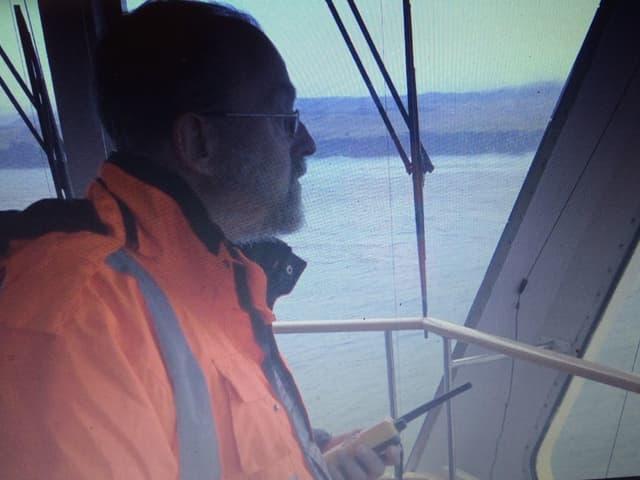 Mann mit Funkgerät auf Schiffsbrücke