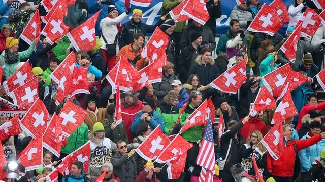 Skifans schwenken die Schweizer Fahne.