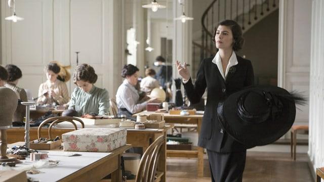Eine Frau mit grossem schwarzem Hut geht durch ein Nähatelier.