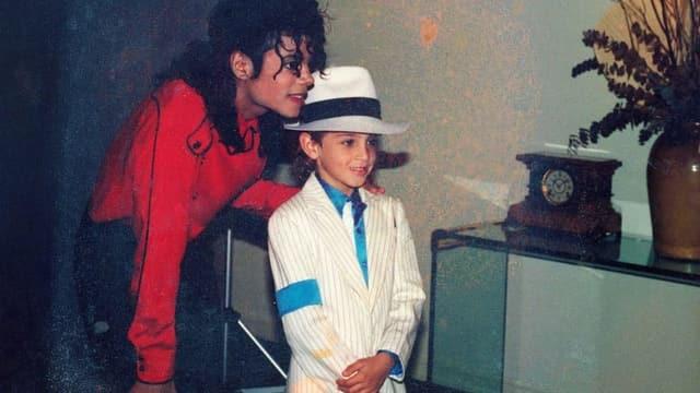 Michael Jackson steht hinter einem kleinen Jungen, hält ihn an der Schulter und posiert für ein Foto.