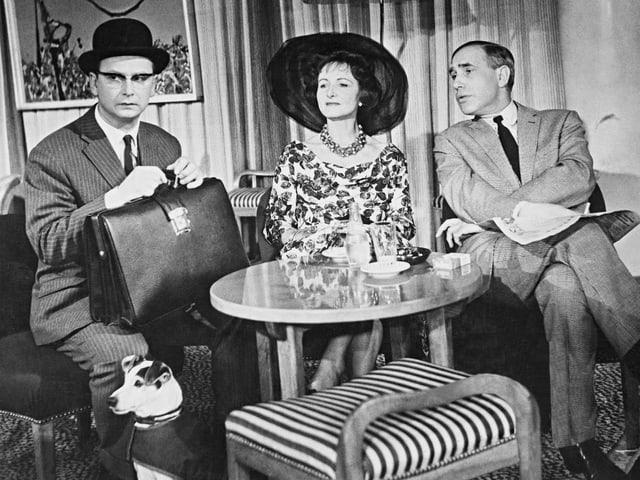 Ein Banker mit einer Aktentasche und einer schwarzen Melone sitzt auf einer Couch. Daneben eine Frau mit Hut und ein Mann mit Anzug.