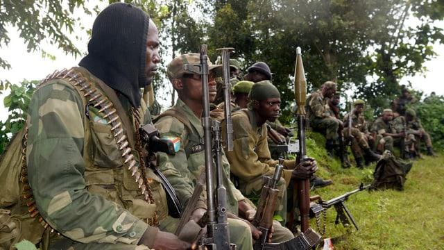 Kongolesische Soldaten sitzen im Gras.