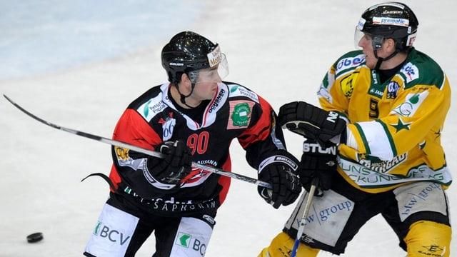 Andreas Küng kämpft gegen einen Lausanner Spieler um den Puck.