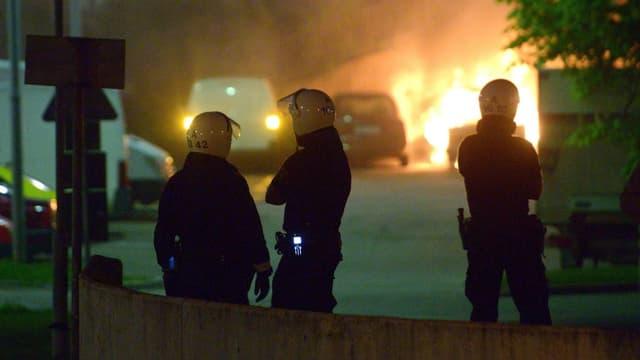 Drei Polizisten mit Helm beobachten ein brennendes Auto aus sicherer Entfernung.