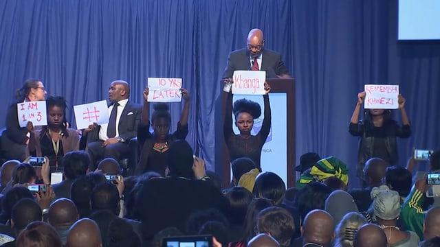 Frauen halten Schilder, Präsident Zuma spricht auf dem Podium