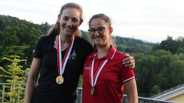 Zwei junge Frauen mit Goldmedaillen um den Hals