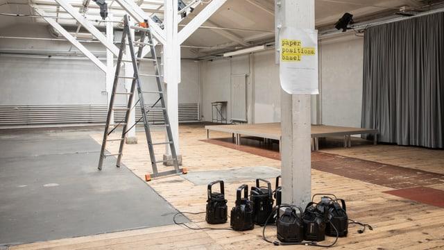 EIn leerer Raum in dem eine Leiter steht, am Boden liegen schwarze Schweinwerfer.