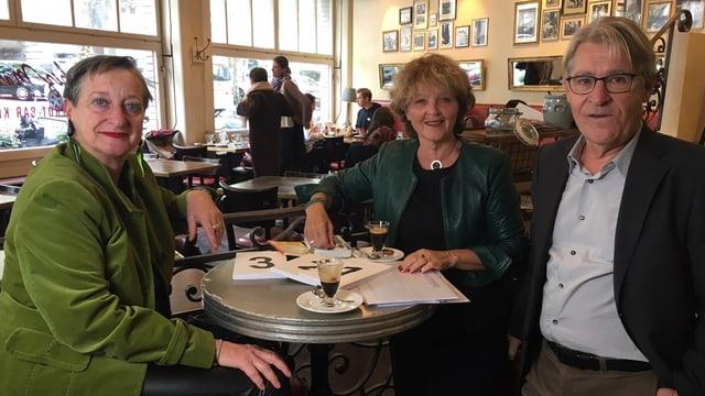 Zwei ältere Frauen und ein Mann an Bistrotisch in Restaurant
