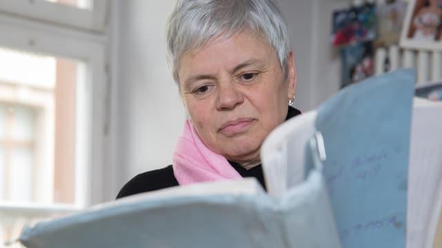 Eine Frau schaut in ein Buch.