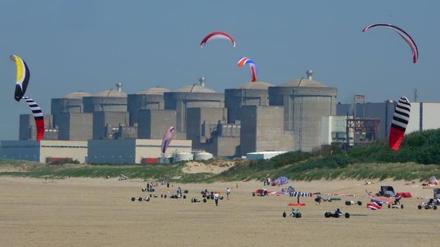 Sechs grosse Betonreaktoren stehen hinter einem Strand, auf dem Personen Drachen steigen lassen.