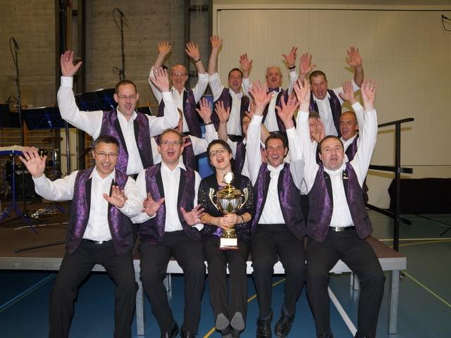 Gruppenbild mit Musikanten und Dirigentin, die mit dem Pokal um die Wette strahlen.