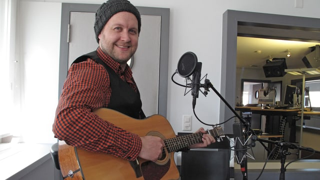 Ein Mann mit Gitarre vor einem Mikrofon.