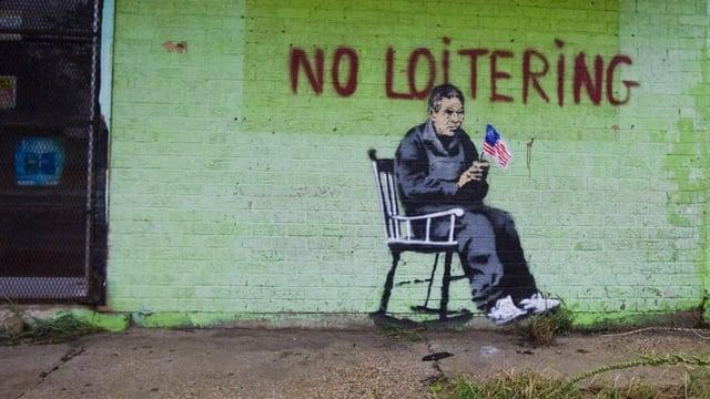 Auf einer Hauswand ist das Bild eines Mannes im Schaukelstuhl zu sehen.