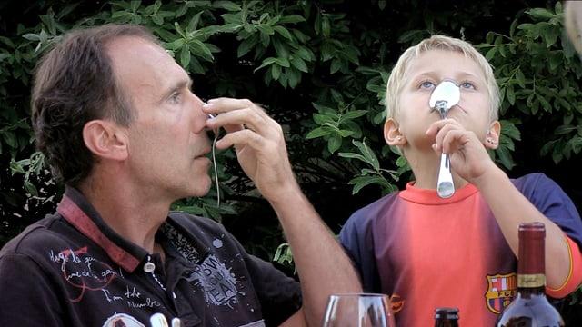 Mann und Kind versuchen, Löffel an die Nase zu drücken, bis sie kleben.