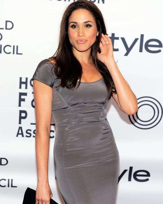 Meghan Markle posiert mit grauem Kleid.