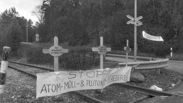 Kreuze mit einem Plakat auf Bahnschienen.