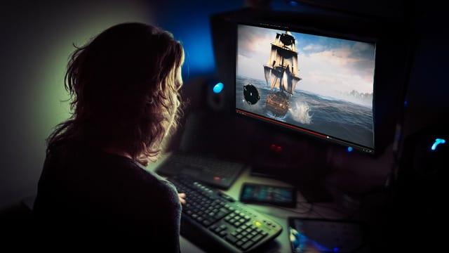 Eine Frau schaut auf einem Computer ein Video eines Computerspiels.