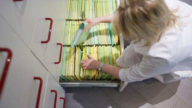 Eine Arzthelferin räumt eine Patientenakte zurück in eine Schublade.