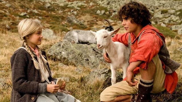 Bild aus dem Film Schellen-Ursli. Zu sehen ist ein Mädchen, eine Geiss und der Schellen-Ursli.