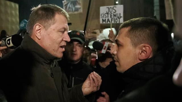 Klaus Iohannis (dretg) en discurs cun in demonstrant sin la Plazza da l'Universitad a Bucarest.