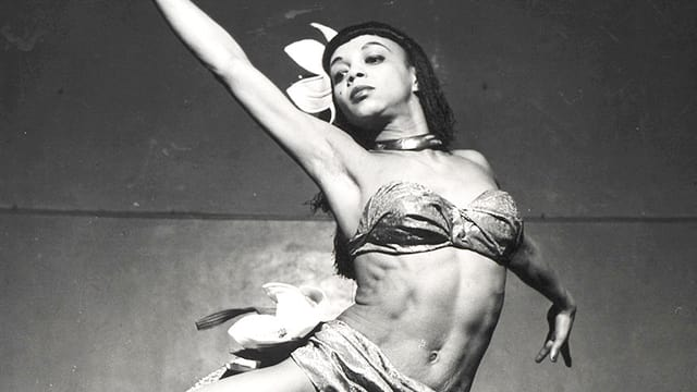 Dallas am Tanzen mit einem Oberteil wie ein Büstenhalter, mit Blumen im Haar, diagonal im Bild.