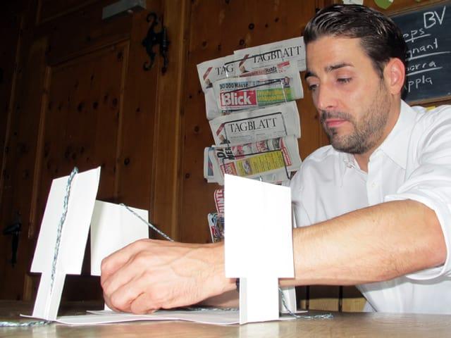 Mann am Tisch, vor sich aufrecht stehende, weisse Papierstreifen.