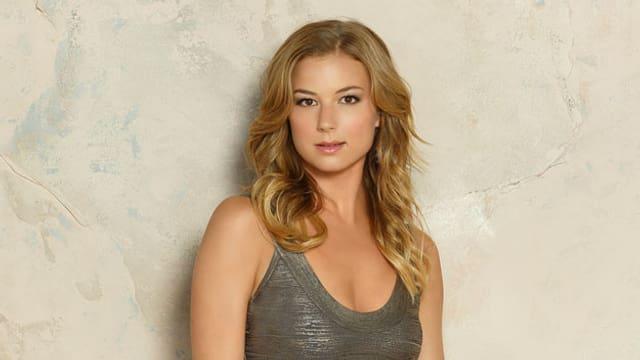 Emily VanCamp in einem grauen, glänzenden Klei mit offenem blondem Haar.