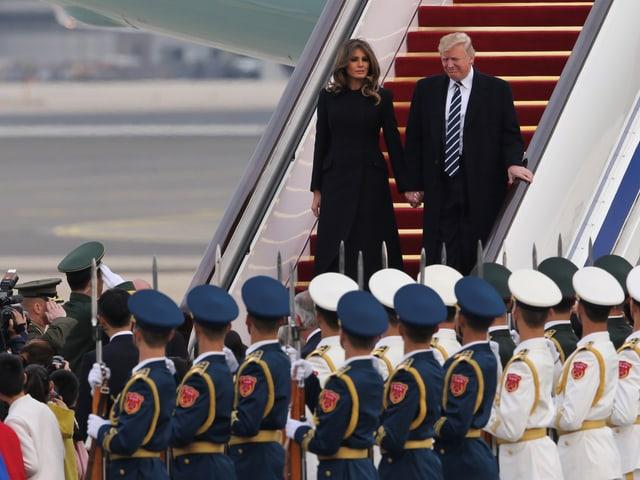 Soldaten in Habachtstellung bilden Spalier für das Präsidentenpaar auf der Flugzeugtreppe.