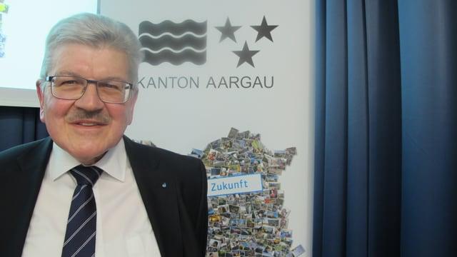 Brogli steht vor einem Flip-Chart mit dem Wappen des Kantons drauf.