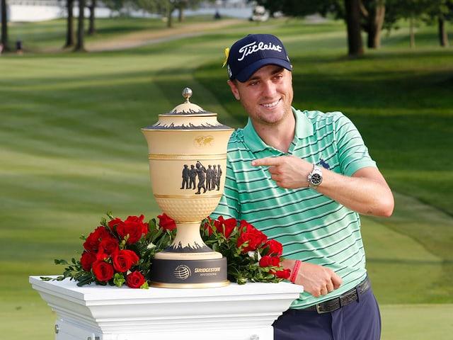 Justin Thomas posiert mit Pokal.