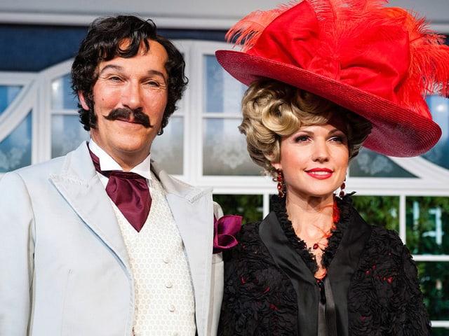 Ein dunkelhaariger Mann mit Schnurrbart und eine blondhaarige Frau mit einem grossen roten Hut.