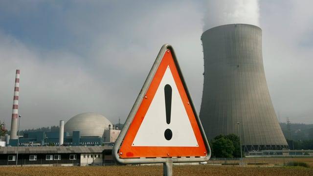 Atomkraftwerk im Hintergrund. Im Vordergrund eine Dreieckstafel mit Ausrufezeichen.