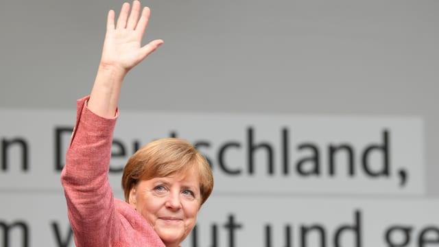 La chanceliera Angela Merkel salida giu d'ina tribuna a chaschun d'ina occurrenza en il cumbat electoral.
